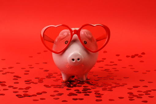Piggy bank in love with red heart sunglasses standing on red background with shining red heart glitters - horizontal
