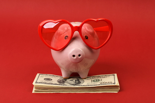 Piggy bank with heart sunglasses standing on stack of money