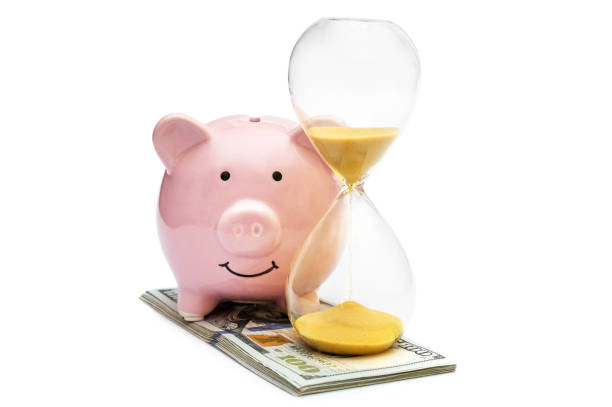 piggy bank with hourglass and money on white. - commercial activity stock photos and pictures