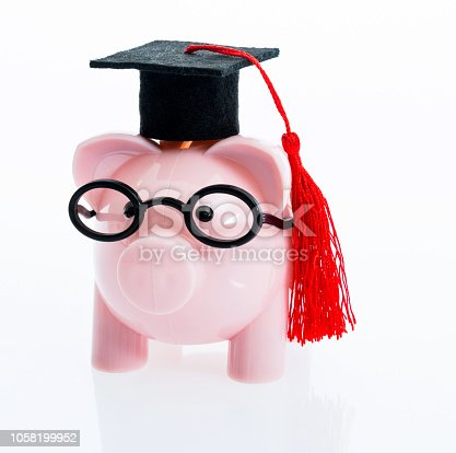 Piggy bank with mortarboard on white background.