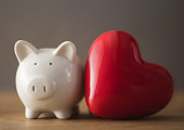 istock Piggy bank with red heart 1184414030