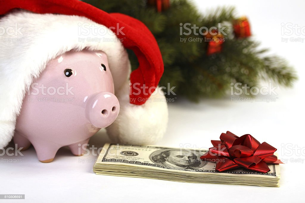 Piggy bank with Santa hat and money, christmas tree stock photo