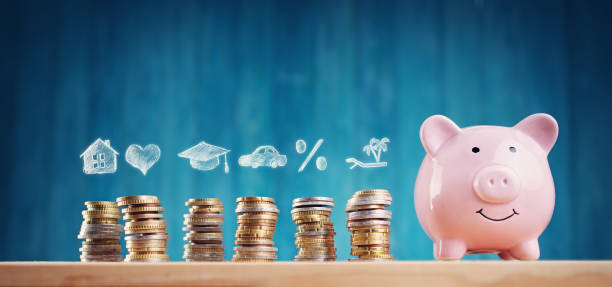 Piggy bank with stacked coins on blue background stock photo