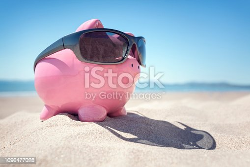 istock Piggy bank with sunglasses on the beach in Summer 1096477028