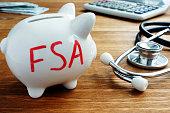 istock Piggy bank with words Flexible Spending Account FSA. 1090754174