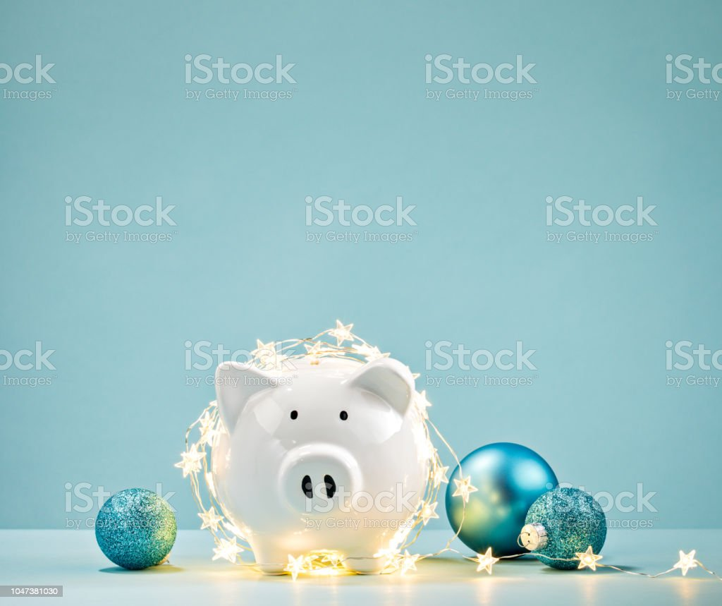 Piggy bank wrapped in a string of Christmas lights stock photo