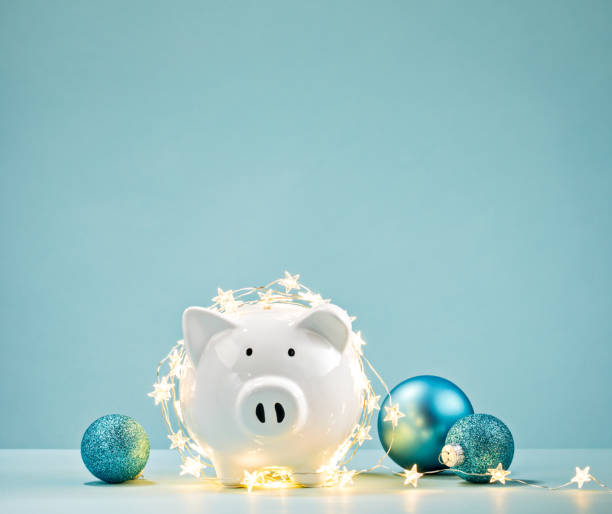 piggy bank wrapped in a string of christmas lights - attività commerciale foto e immagini stock