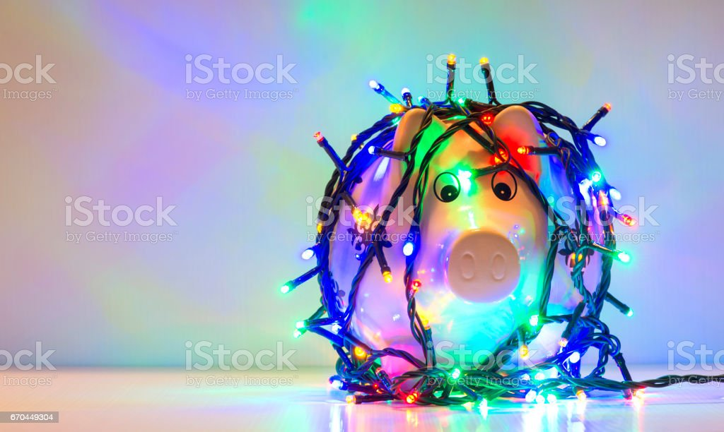 Piggy bank wrapped in Christmas string lights stock photo
