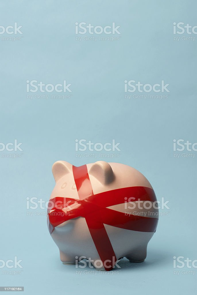 Piggy bank wrapped in red tape stock photo