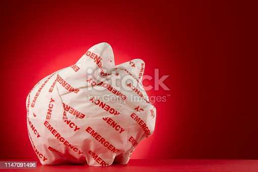 Piggy bank wrapped with emergency paper in front of a red background