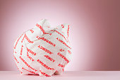 Piggy bank wrapped with emergency paper in front of a pink background