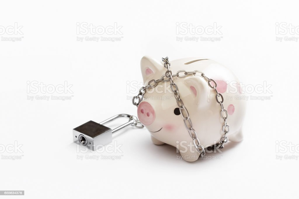 Piggy banks is lock by chain and key on white background, saving and financial concept stock photo