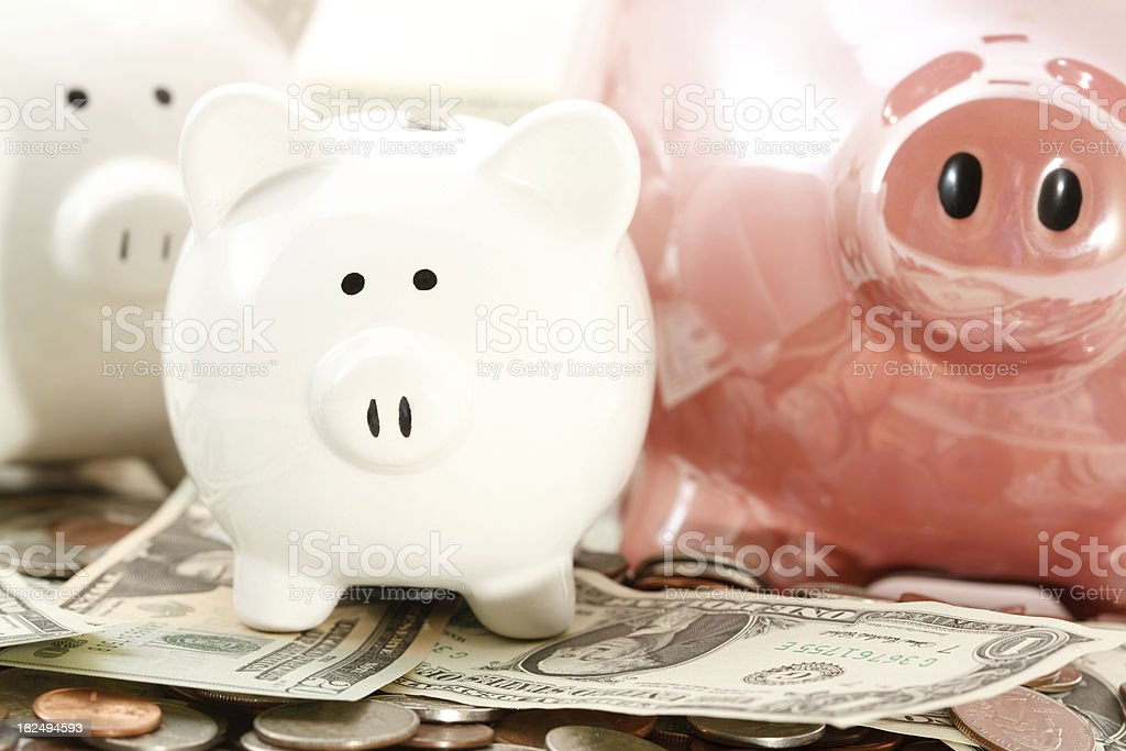 Piggy Banks Laying on Piles of Cash royalty-free stock photo