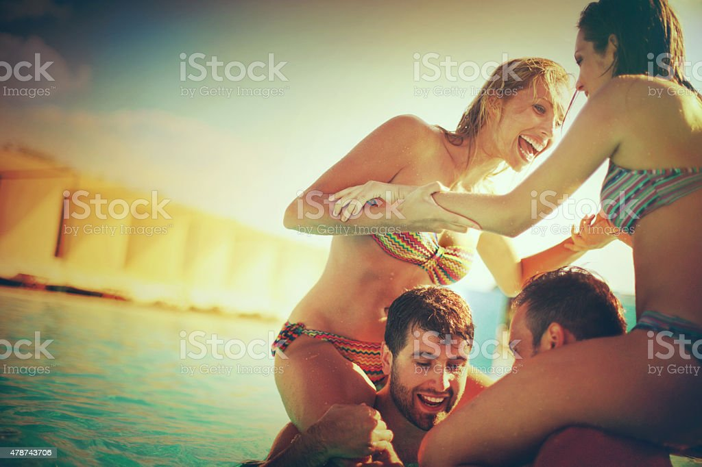 Piggyback fight at swimming pool. stock photo