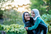 A Muslim woman and her daughter are outdoors in a public park on a sunny day. They are wearing casual clothes and head scarves. The mother is giving her daughter a piggyback ride.