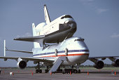 Horizontal, color image of an Angular view of one of NASA's space shuttles sitting, or mounted, on top of a 747 jet aircraft used to move it from its landing point back to the launching site in Florida, U.S.A.  This was taken at Ellington Airforce Base in Texas, U.S.A. in the afternoon.