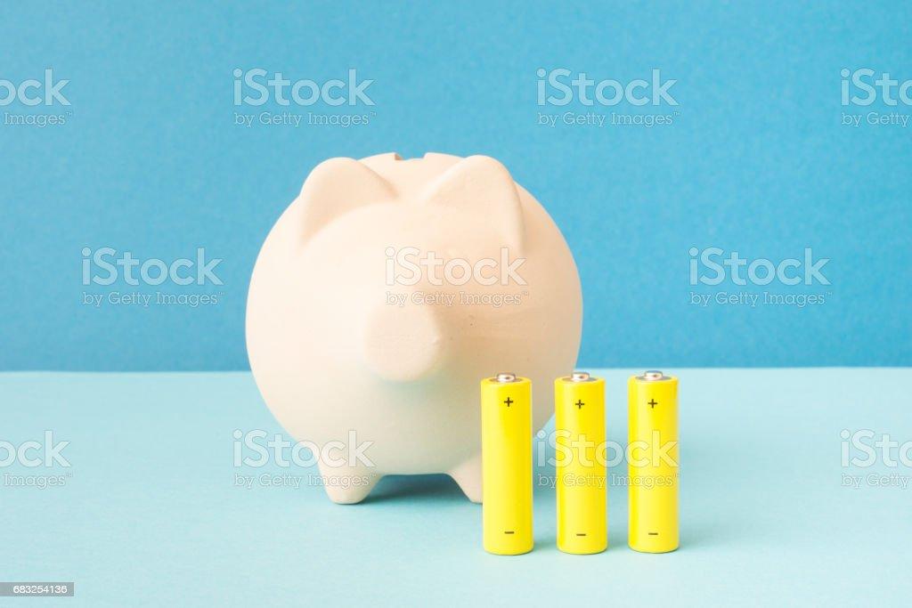 Piggybank and battery stock photo