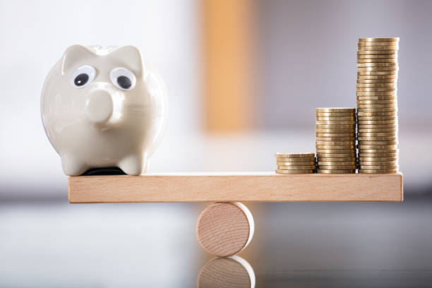 Piggybank And Stacked Coins On Seesaw Close-up Of Piggybank And Stacked Coins Balancing On Wooden Seesaw 40 kilometre stock pictures, royalty-free photos & images