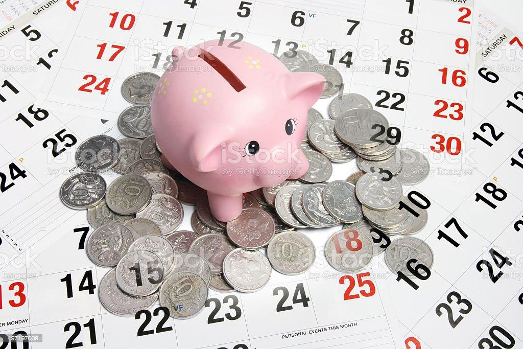 Piggybank, Coins and Calendar Composite of Piggybank, Coins and Calendar Business Stock Photo