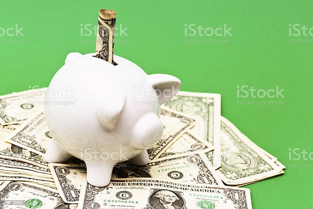 Piggybank guardian stands over pile of US banknotes royalty-free stock photo