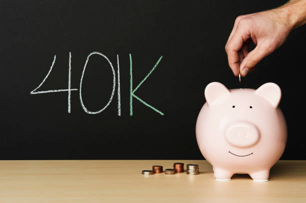 """Piggybank on wooden table with stacks of coins beside it. A hand putting a coin into the piggy bank. Piggybank on wooden table with stacks of coins beside it. A hand putting a coin into the piggy bank with""""401k"""" written in chalk beside it. 401k stock pictures, royalty-free photos & images"""