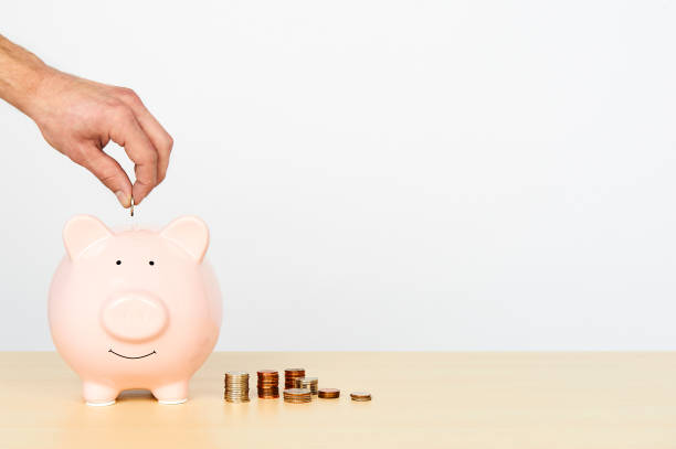 Piggybank on wooden table with stacks of coins beside it. A hand putting a coin into the piggy bank. stock photo