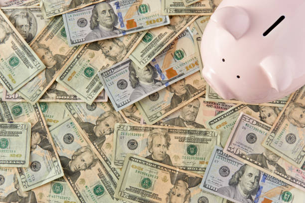 Piggybank surrounded by paper money resting on a table. stock photo