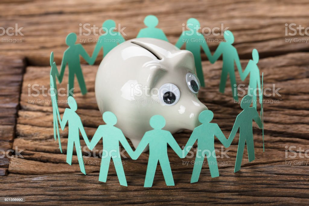 Piggybank Surrounded By Paper People Holding Hands On Wood stock photo