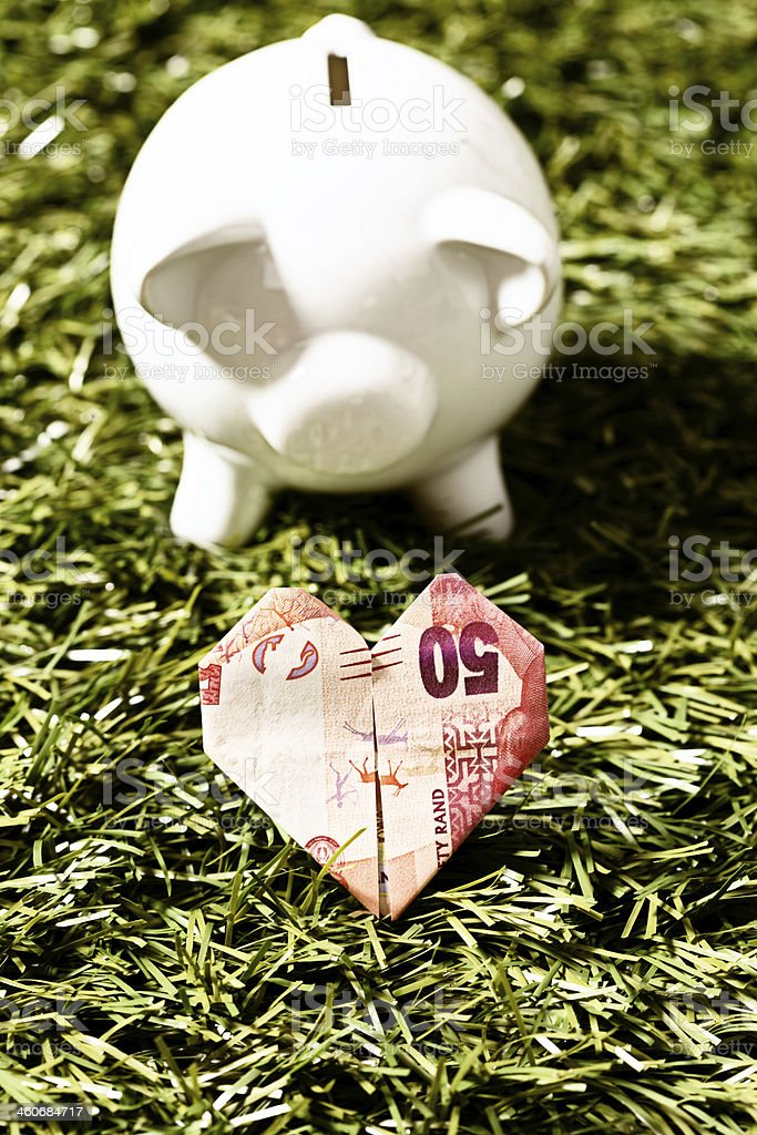 Piggybank watches over origami heart folded from Fifty Rand banknote stock photo