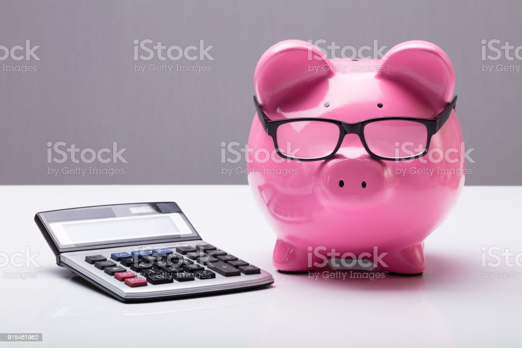Piggybank With Eyeglasses And Calculator stock photo