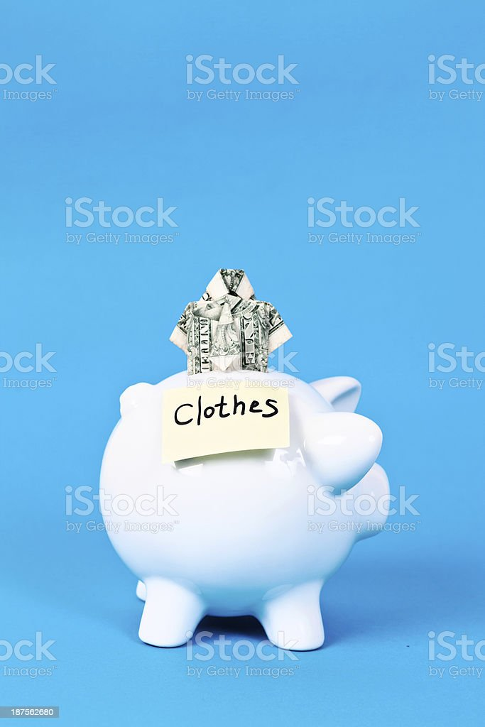 Piggybank with origami shirt is saving for clothes royalty-free stock photo