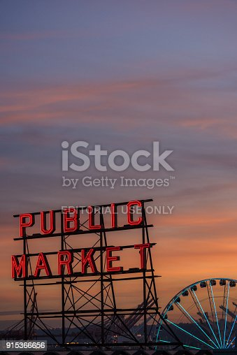Seattle:, USA - Jan 3, 2018: The famous Pike Place Public Market sign at sunset with the Ferris wheel.