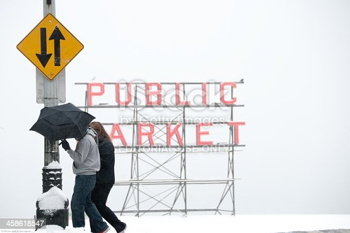 Seattle, Washington, USA – January 18th 2012: A couple crossing the street at 1st and Pine street in front of the famous Pike Place Market sign during a rare winter storm in downtown Seattle.