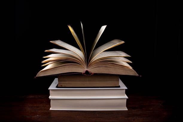 Pila di Libri con libro aperto Pila di Libri con libro aperto su sfondo nero libro stock pictures, royalty-free photos & images
