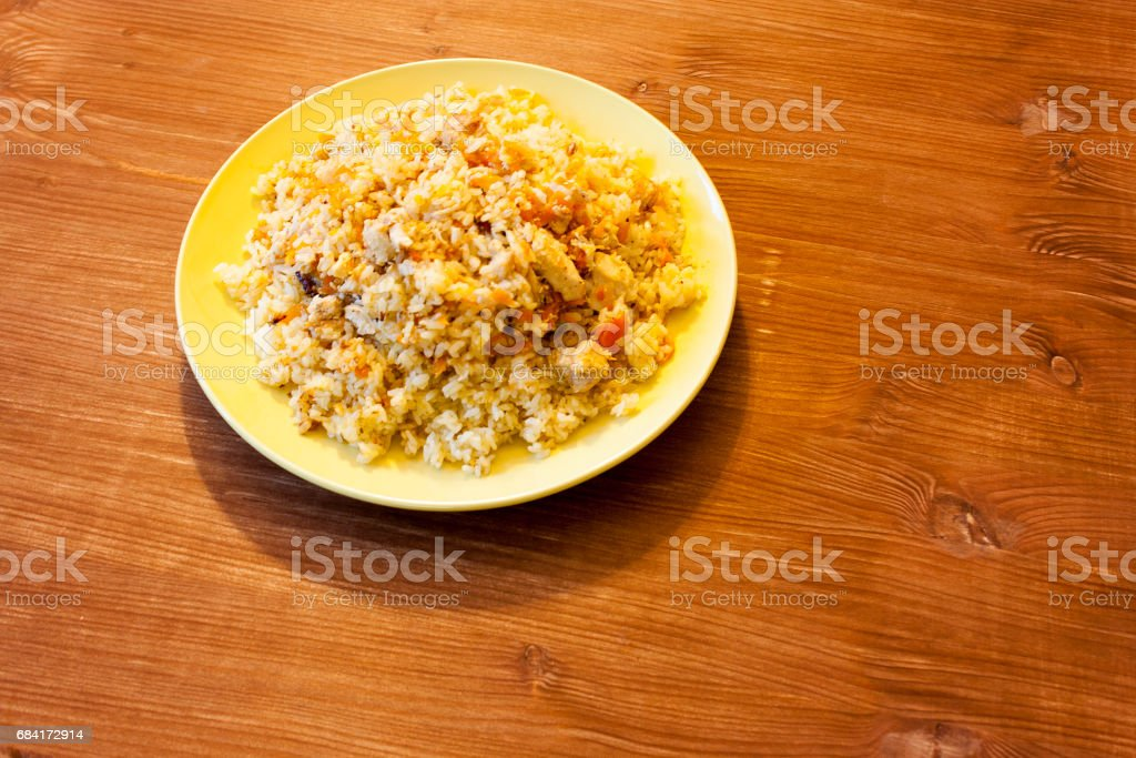 Pilaf on the clay plate on a wooden table. zbiór zdjęć royalty-free