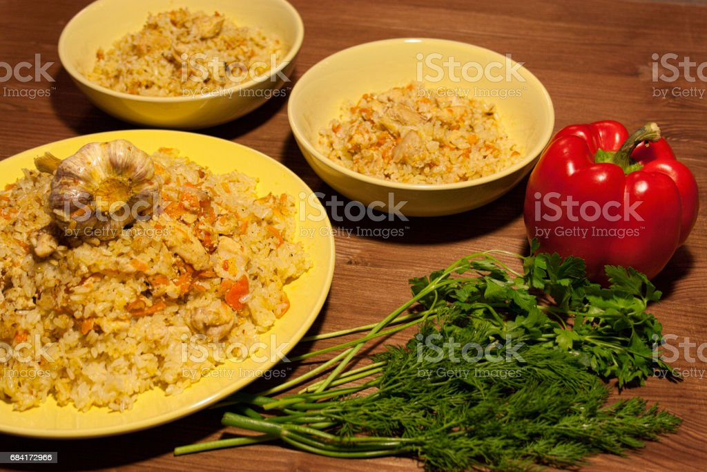 Pilaf on the clay plate on a wooden table. foto stock royalty-free