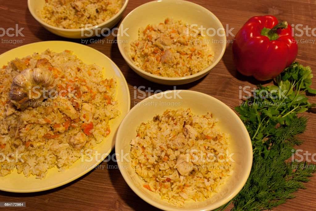 Pilaf on the clay plate on a wooden table. royalty-free stock photo