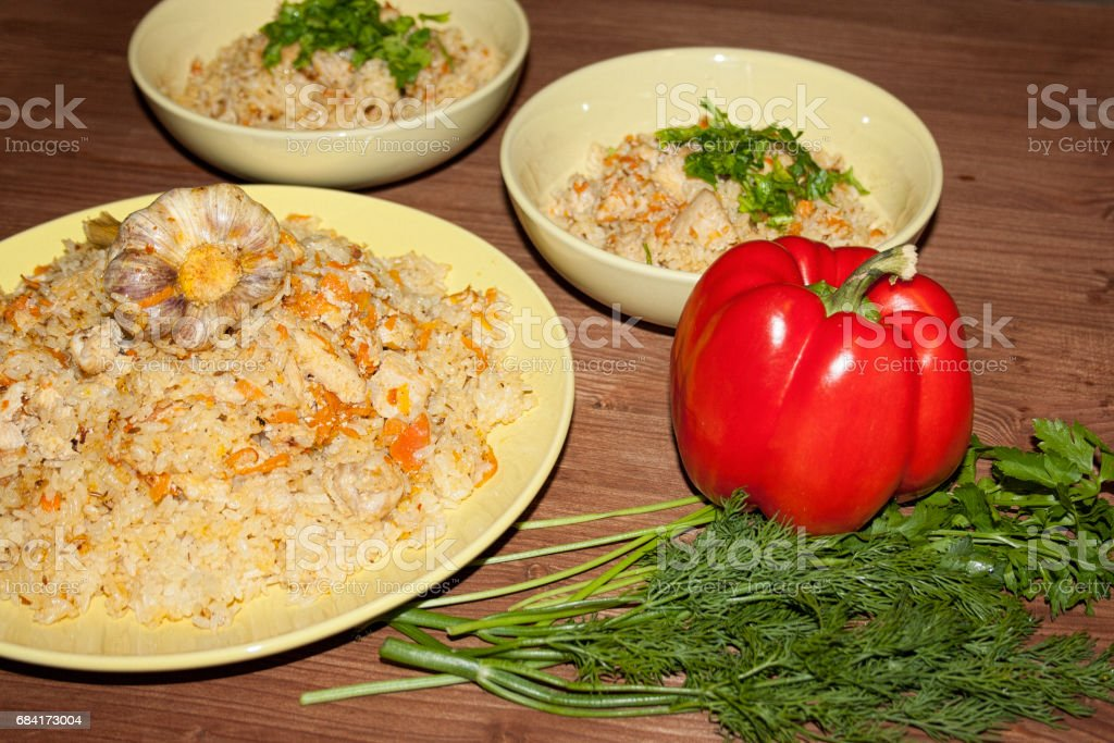 Pilaf on the clay plate on a wooden table. photo libre de droits