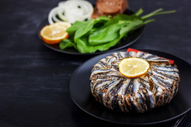 pilaf con pescado de anchoa de hamsi. comida tradicional turca - kapama pilav - sobre mesa de madera negra. - anchoa fotografías e imágenes de stock