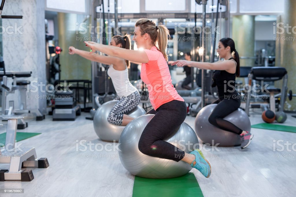 Group Of Young Women Doing Sports Training Drill With Pilates Ball.