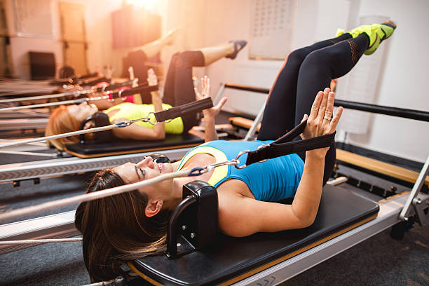 Pilates exercises on machines in a health club. stock photo