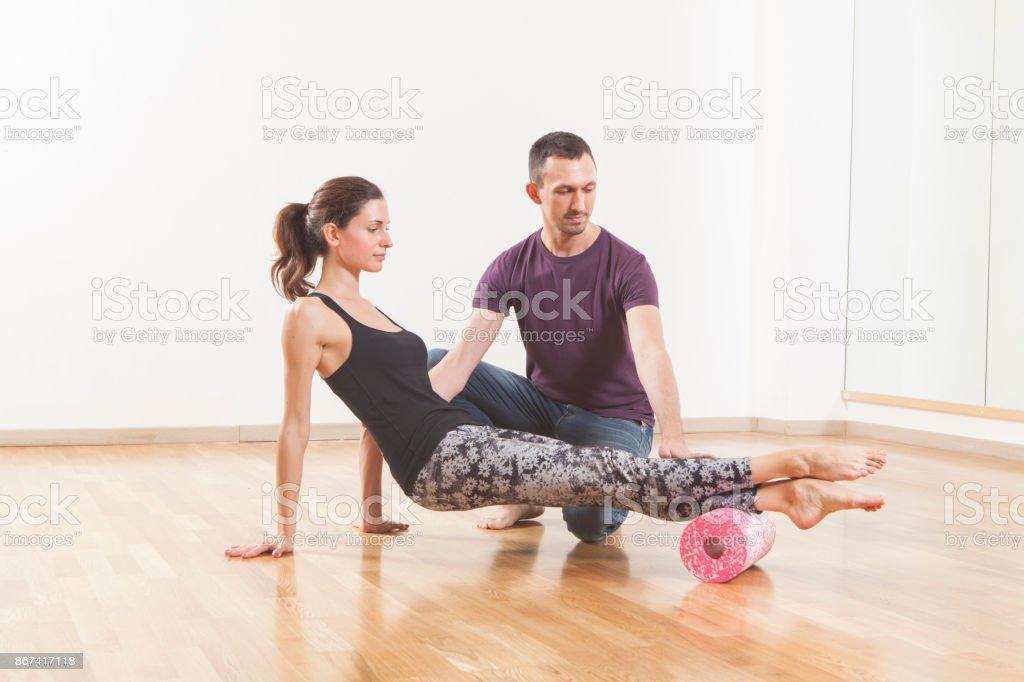 Pilates instructor coaching a beautiful woman using foam roller stock photo
