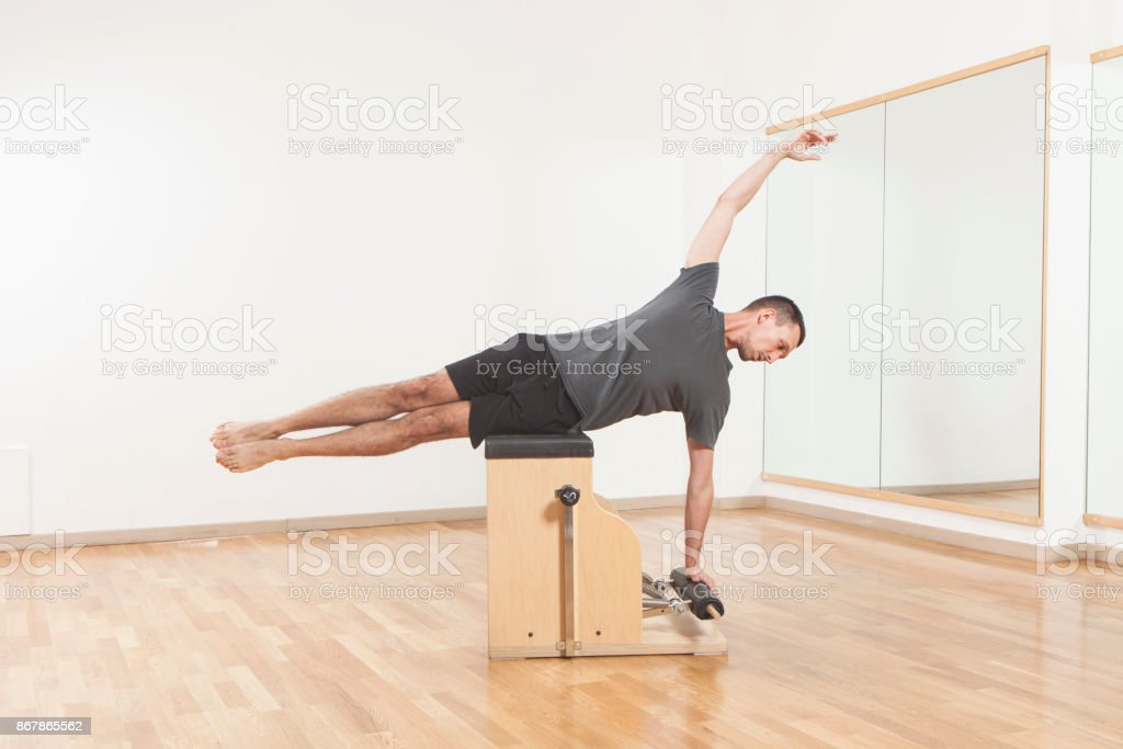 Pilates instructor performing fitness exercise on chair equipment stock photo