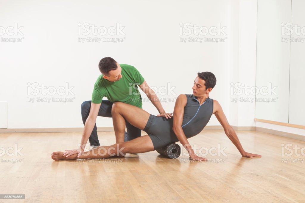 pilates instructor teaching a ballet dancer using foam roller stock photo
