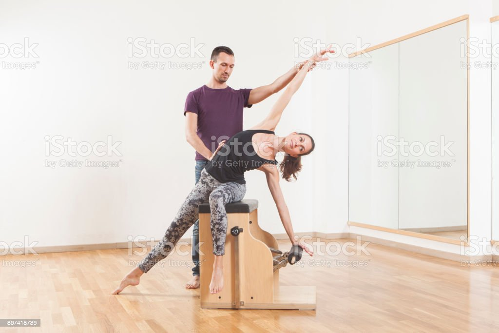 Pilates lesson on barrel, personal trainer coaching young beautiful woman stock photo