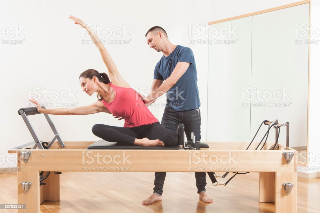 Pilates lesson on reformer, personal coaching young beautiful woman stock photo