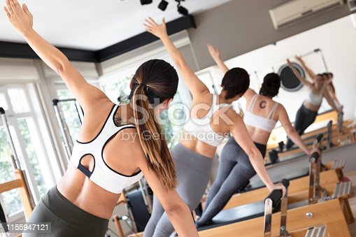 Three females doing side plank on reformer in pilates studio.