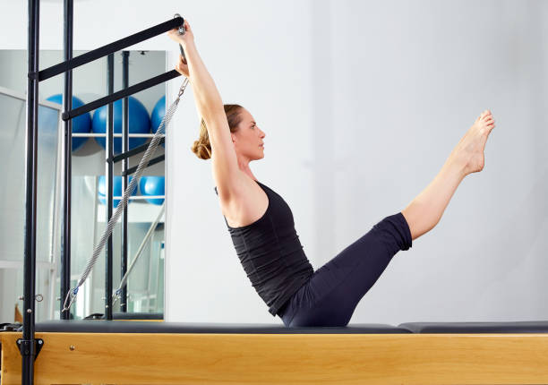pilates woman in reformer teaser exercise at gym - metodo pilates foto e immagini stock