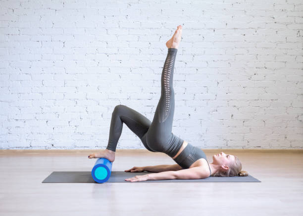 pilates workout. woman in grey sports suit doing exercise on math with fitness roller, loft style background, toned light blue - metodo pilates foto e immagini stock