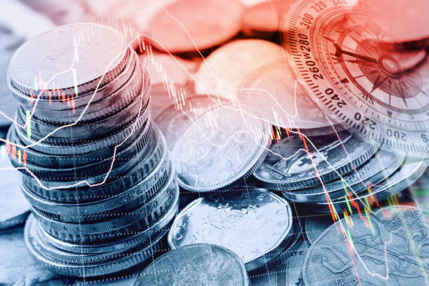 Pile and a stack of coins with technical chart of financial instruments. stock photo